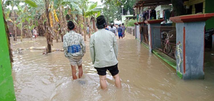 Warga Kaliwungu melewati jalan yang kembali banjir pada Jumat (5/2). [Doc.Dzikkri/Pelajarkudus]